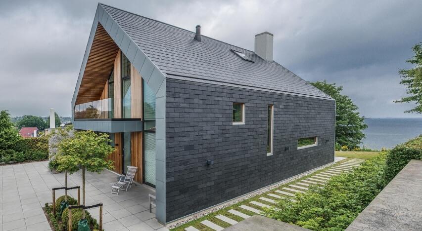 Imponerende hus med naturskifer facadebeklædning og store vinduer.