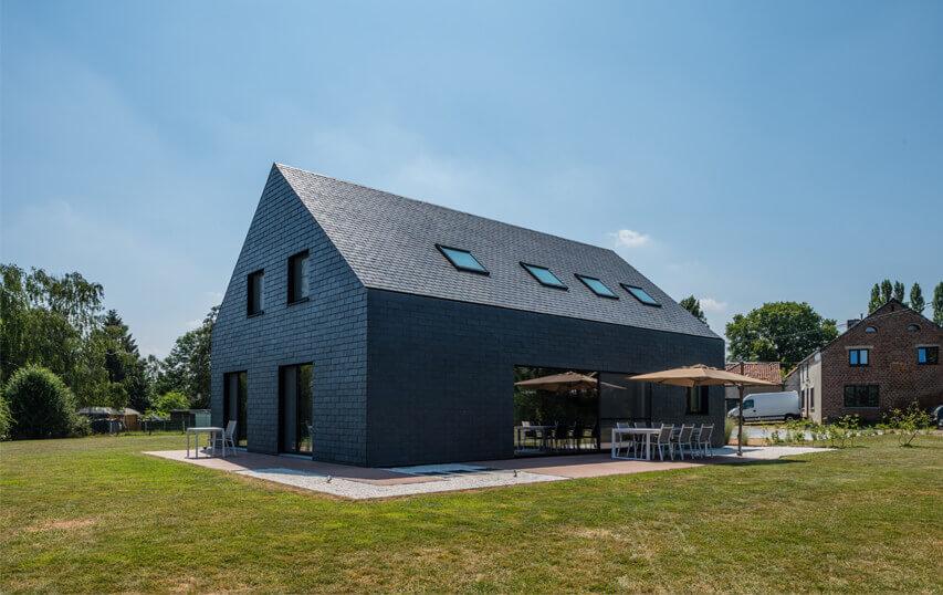 Imponerende hus med naturskifer facade og sadeltag.