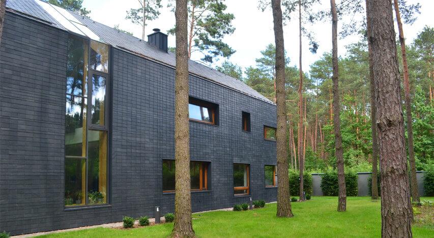 Et moderne hus designet med naturskifer, træ og høje vinduer