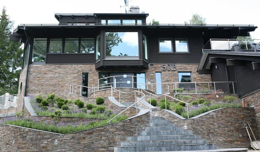 moderne villa med en træ- og naturstensfacade.